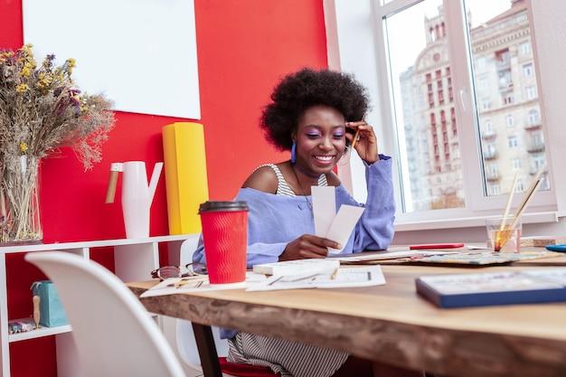 Kawa i praca. inspirowana kreatywnością projektantka mody pije kawę i ciężko pracuje w biurze