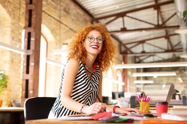 Kawa i praca. rozpromieniona rudowłosa kobieta pijąca kawę i pracująca, czując się naprawdę szczęśliwa