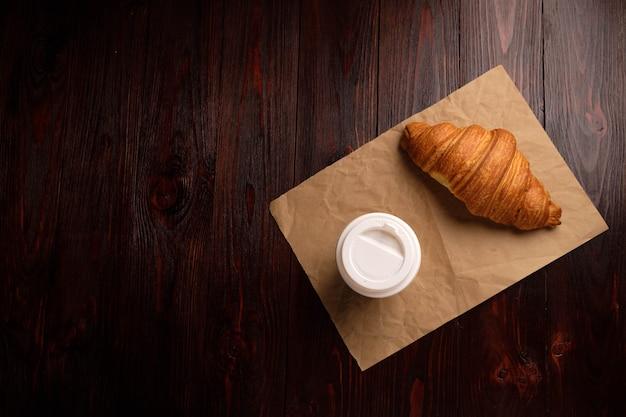 Kawa i rogalik na drewnianym stole