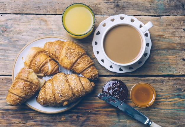 Kawa i rogaliki z dżemem i sokiem pomarańczowym. typowe francuskie śniadanie (petit déjeuner)