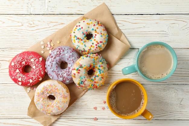 Kawa i smaczne pączki na podłoże drewniane