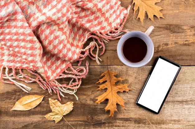 Kawa i szalik na drewnianym tle