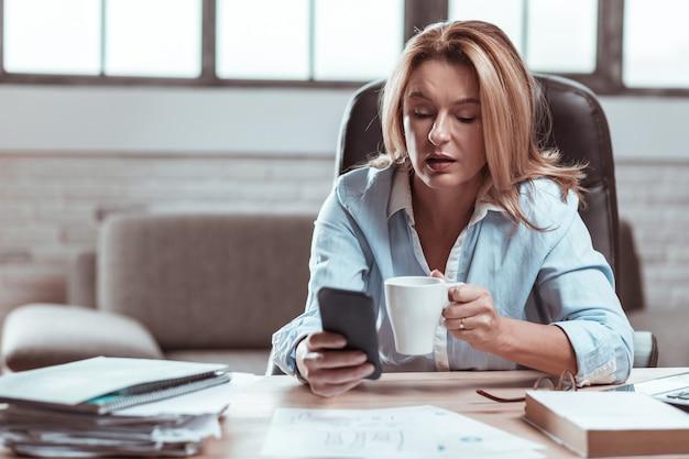 Kawa i telefon. blondynka dojrzała bizneswoman ciesząca się przerwą na picie kawy i korzystanie ze smartfona