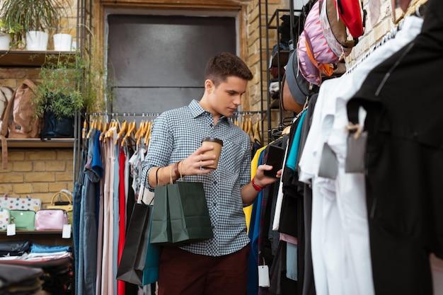 Kawa i zakupy. spokojny, zrelaksowany młody człowiek czuje się dobrze trzymając filiżankę kawy i patrząc na modne ubrania w sklepie