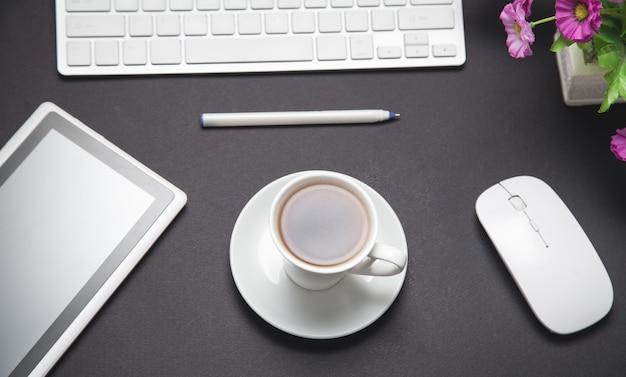 Kawa, klawiatura komputerowa, mysz, długopis, tablet. nowoczesne biurko biznesowe w kolorze czarnym. gabinet