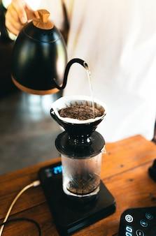 Kawa kroplowa, barista nalewający wodę na zmieloną kawę z filtrem, zaparzanie kawy