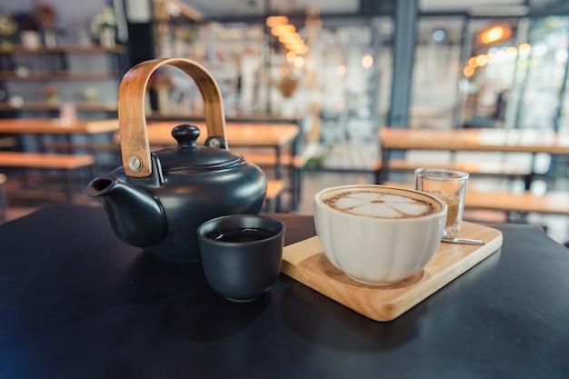 Kawa latte art, filiżanka gorącej kawy na drewnianej tacy i ciemnym stole