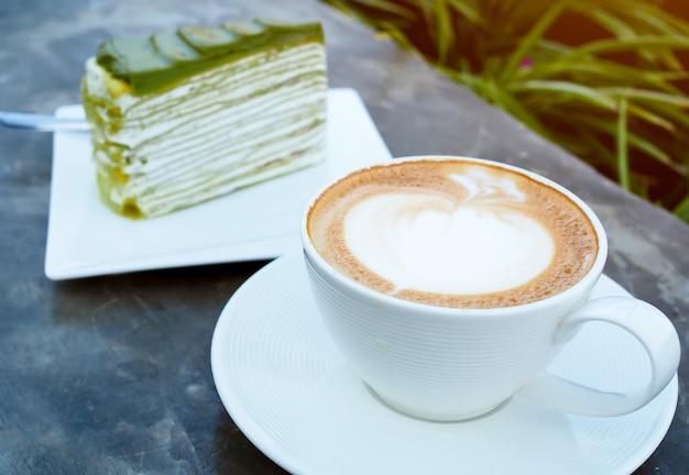 Kawa latte lub cappuccino w białej filiżance z ciastem zielonej herbaty na stole