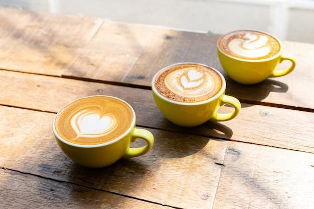 Kawa latte lub kawa cappuccino w żółtej filiżance z pięknym sercem latte art na drewnianym stole.