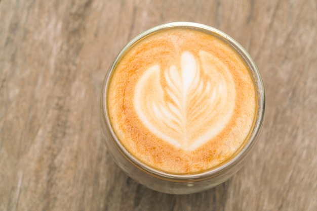 Kawa latte sztuki na drewnianym stole.