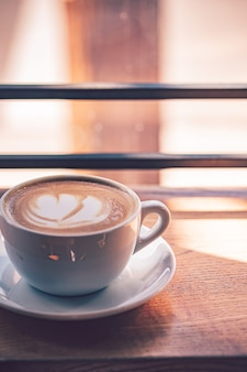Kawa latte w białej filiżance na drewnianym stole przed dużym oknem kawiarni.