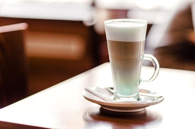 Kawa latte w dużej szklance stoi na stoliku w kawiarni. poziome zdjęcie