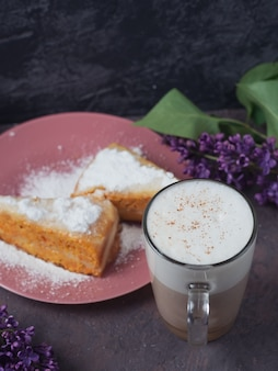Kawa latte w szklanej szklanej szklanej szklance z kawałkiem ciasta