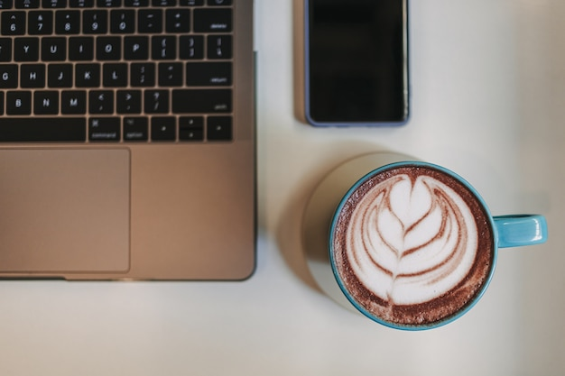 Kawa latte z laptopem i telefonem komórkowym