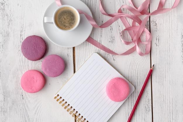 Kawa, macaron z ciasta, czysty notatnik, okulary i kwiatek na różowym stole z góry.