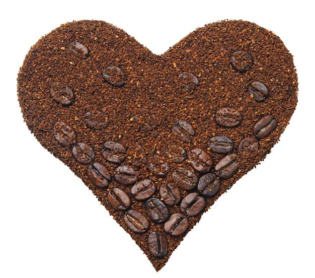 Kawa mielona i ziarna kawy w kształcie serca na białym tle