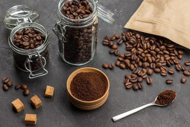 Kawa mielona w drewnianej misce i łyżce. palona kawa ziarnista w szklanym słoiku oraz w papierowej torebce. kawałki brązowego cukru na stole. widok z góry.