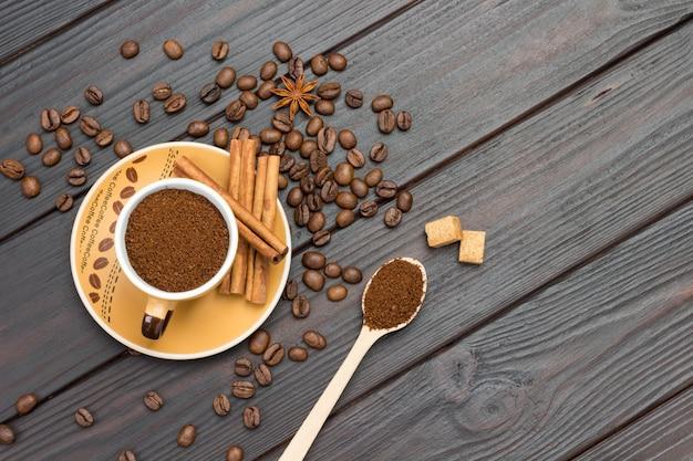 Kawa mielona w filiżance i w drewnianej łyżce. laski cynamonu na spodku. ziarna kawy i anyż gwiazdkowaty na stole. ciemne tło drewna. leżał płasko. skopiuj miejsce