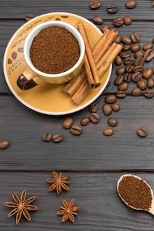 Kawa mielona w filiżance i w drewnianej łyżce. laski cynamonu na spodku. ziarna kawy i anyż gwiazdkowaty na stole. ciemne tło drewna. płaskie ułożenie
