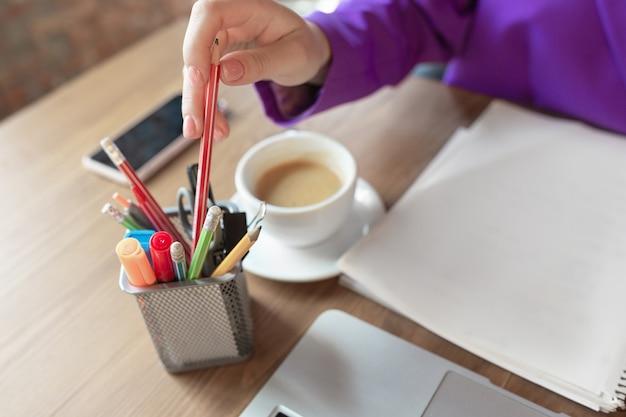 Kawa. młoda biznesowa kaukaski kobieta pracująca w biurze, wygląda stylowo. papierkowa robota, analizowanie, szukanie decyzji. pojęcie finansów, biznesu, girl power, inkluzji, różnorodności, feminizmu zbliżenie