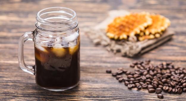 Kawa mrożona i ziarna kawy w tle.