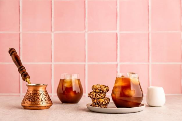 Kawa mrożona na zimno w szklance, podawana z ciasteczkami owsianymi. cezve i biały dzbanek na mleko. ciepłe światło i jasny obraz, różowe tło płytek