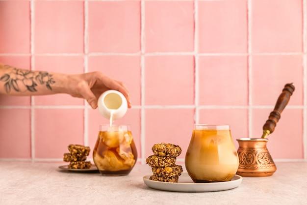 Kawa mrożona na zimno w szklance, podawana z ciasteczkami owsianymi. dżezwa. kobieca ręka z kwiatami tatuaż wylewa mleko z białego dzbanka. ciepłe światło i jasny obraz, różowe tło płytek
