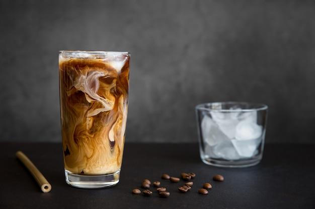 Kawa mrożona w wysokiej szklance z kremowym pojemnikiem z mrożonymi ziarnami kawy