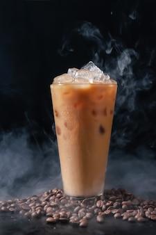 Kawa mrożona z mlekiem w wysokim szkle i ziaren kawy na ciemnym tle