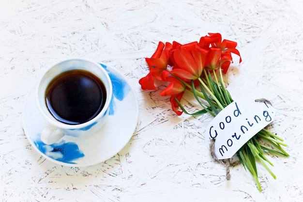 Kawa na białym tle i kwiatach. tulipan. wiosna. ranek. 8 marca. dzień kobiet