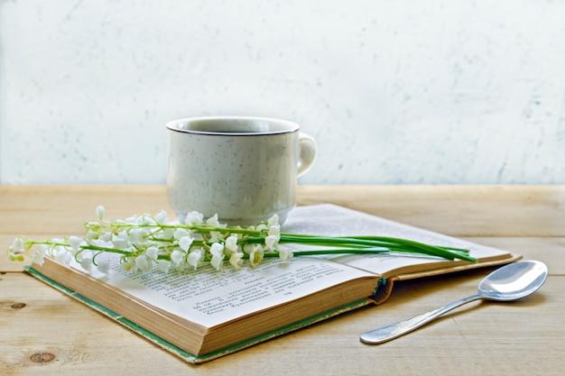 Kawa na drewnianym tle i kwiatach. konwalie. wiosna.