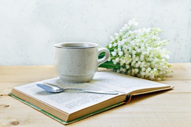 Kawa na drewnianym tle i kwiatach. konwalie.