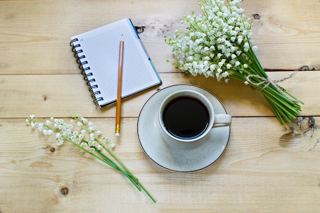 Kawa na drewnianym tle i kwiatach.