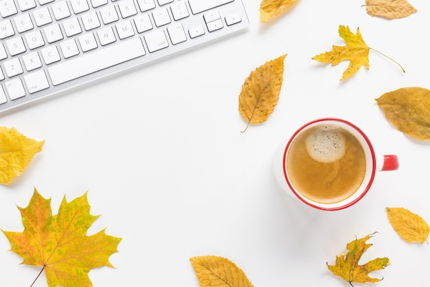 Kawa na klawiaturze komputera i żółte jesienne liście