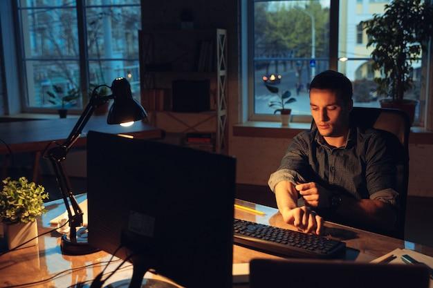 Kawa na ratunek. mężczyzna pracujący samotnie w biurze podczas kwarantanny koronawirusa lub covid-19, przebywający do późna w nocy. młody biznesmen, kierownik wykonujący zadania z smartphone, laptop, tablet w pustym obszarze roboczym.