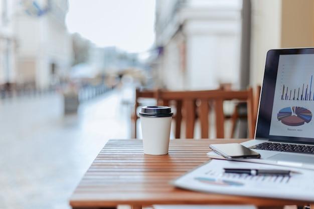 Kawa na wynos i laptop z wykresem finansowym na stoliku w kawiarni.