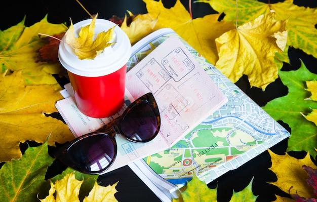 Kawa na wynos, liście, mapa, okulary przeciwsłoneczne i paszport