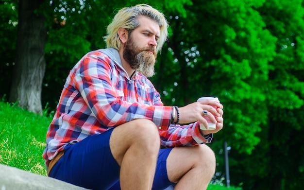 Kawa na wynos. rozważny mężczyzna z kawą plenerową. brodaty mężczyzna z papierową filiżanką kawy.