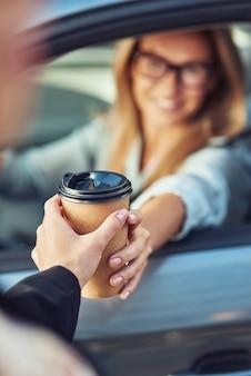 Kawa na wynos, szczęśliwa kaukaska bizneswoman siedzi za kierownicą swojego nowoczesnego samochodu i kupuje kawę na wynos, skup się na papierowym kubku, ludziach i transporcie, koncepcji pojazdu