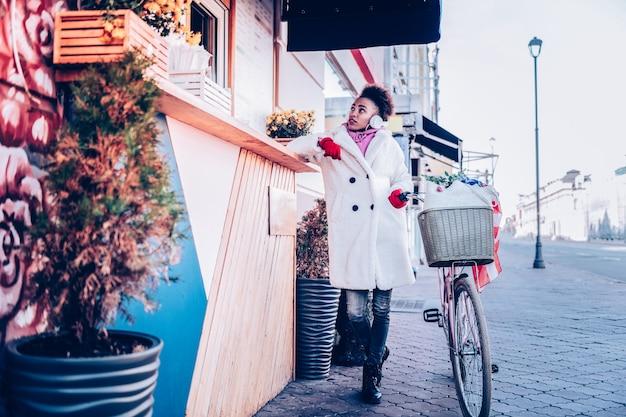 Kawa na wynos. urocza międzynarodowa suczka ubrana w eko futro podczas spaceru po ulicy