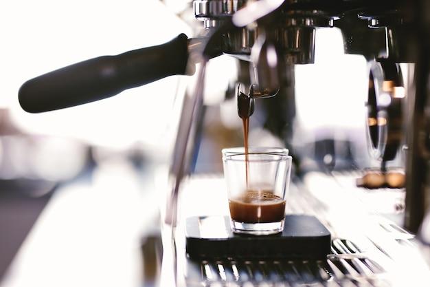 Kawa nalewa się do filiżanki w przytulnej kawiarni. .
