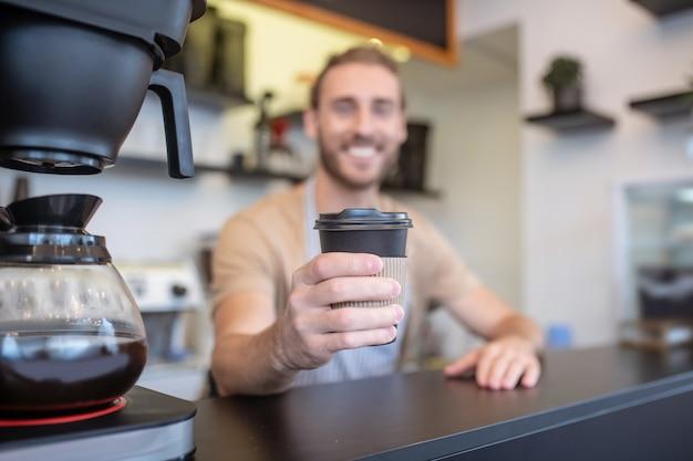 Kawa, nastrój. kieliszek pysznej świeżo zaparzonej kawy w wyciągniętej dłoni uśmiechnięty młody dorosły barista stojący za kontuarem barowym