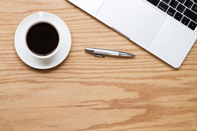 Kawa obok pióra i laptopa