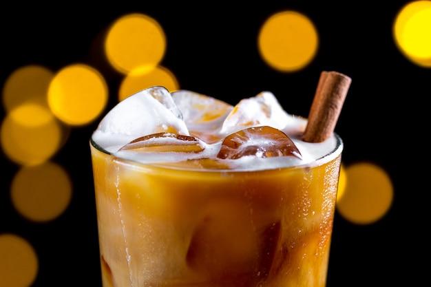 Kawa, orzeźwiający koktajl z kostkami lodu, pianką i cynamonem na powierzchni świateł. zimne napoje