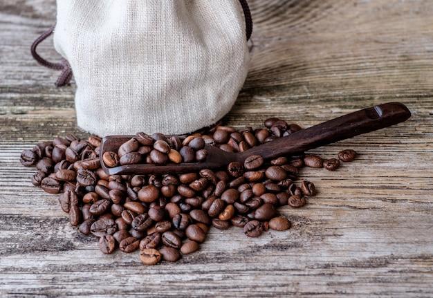 Kawa palona ziarnista w drewnianej łyżce na drewnianym stole obok płóciennej torby