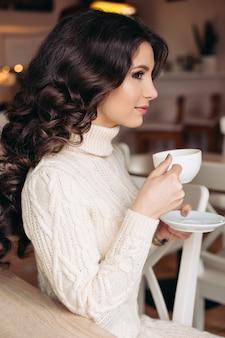 Kawa. piękna kobieta picia herbaty lub kawy. kubek gorącego napoju. brunetka w kawiarni pije herbatę, je słodycze, czyta książkę, piękne oczy i wspaniały makijaż, falowane włosy.