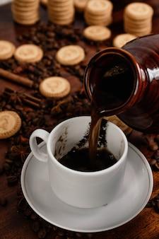 Kawa po turecku nalewająca kawę do filiżanki