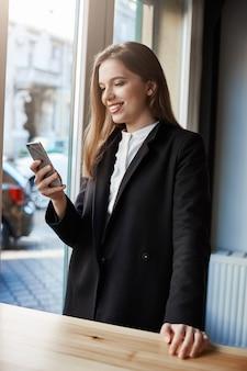 Kawa przed biznesem. portret elegancka pomyślna miastowa kobieta stoi blisko kawiarnia kontuaru