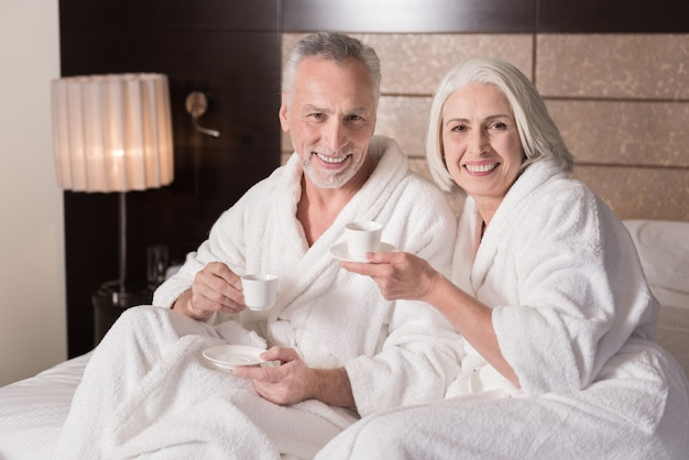Kawa rano. wesoła uśmiechnięta para w wieku leżąc na łóżku i pijąc kawę, wyrażając radość