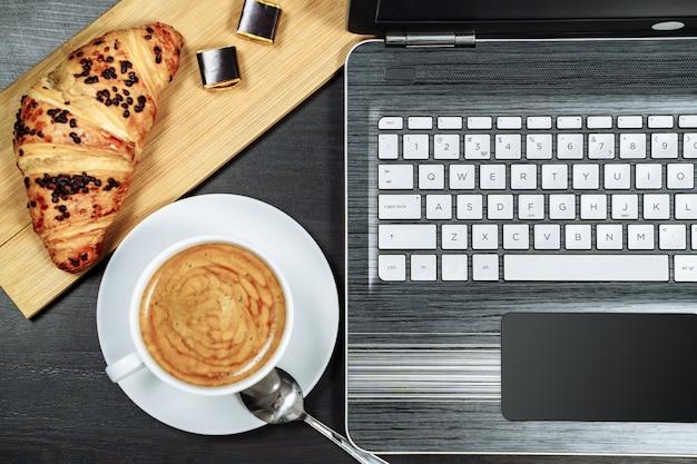 Kawa, rogalik i laptop na stole. śniadanie.